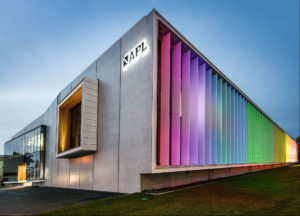 Exterior photograph of APL building with rainbow lighting at night in Hamilton, New Zealand